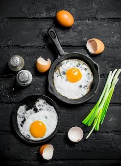 파와 조미료를 곁들인 달걀 프라이. 검은 소박한 배경.