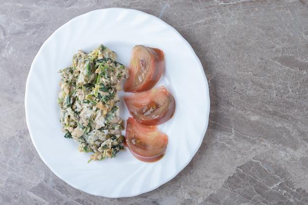 Uovo fritto con verdure e pomodori sul piatto bianco.