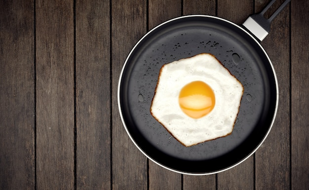 Fried egg with hexagon shape on frying pan on wooden
