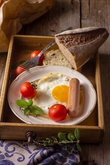 Fried egg with hotdog and tomatoes