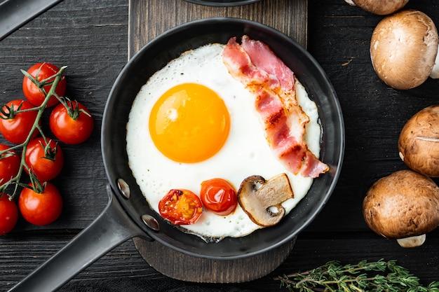 Жареное яйцо с ингредиентами в чугунной сковороде на фоне черного деревянного стола, плоская планировка, вид сверху