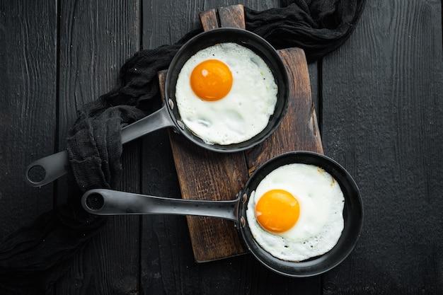 검은 나무 테이블 배경에 주철 프라이팬에 재료로 튀긴 계란, 평면도 평면 누워