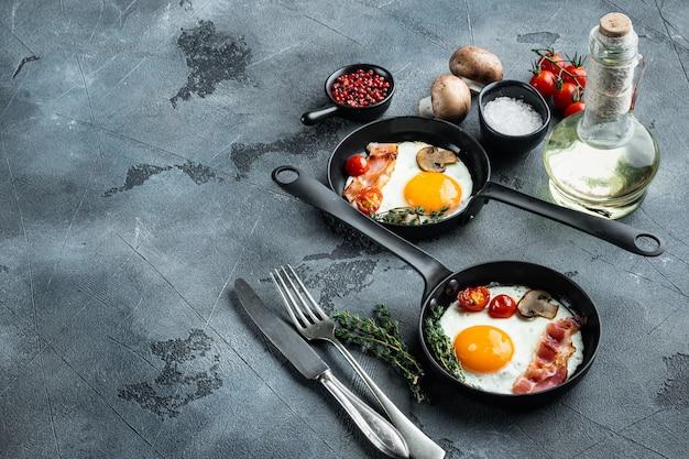 Жареное яйцо с ингредиентами в чугунной сковороде, на сером фоне,