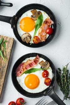 Жареное яйцо с ингредиентами в чугунной сковороде, на белом фоне, плоская планировка, вид сверху