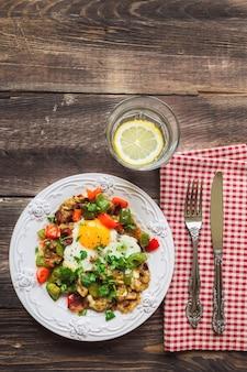 Жареные яйца с перцем, беконом, картофелем и кинзой на деревенском деревянном столе. вид сверху.
