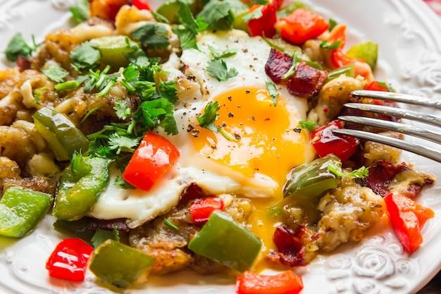 Жареные яйца с перцем, беконом, картофелем и кинзой. выборочный фокус.