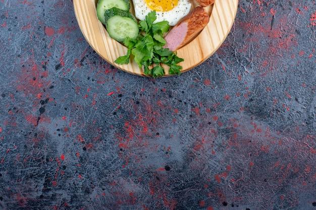 木の板にソーセージ、キュウリ、ハーブを入れた目玉焼き。