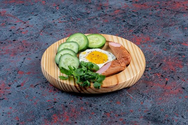 Uovo fritto con salsiccia, cetriolo ed erbe aromatiche in un piatto di legno.