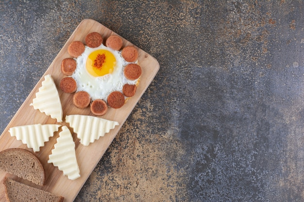Жареное яйцо с сосисками и ломтиками сыра на деревянном блюде