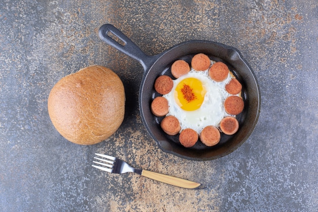 Яичница с сосисками на сковороде с хлебной булочкой