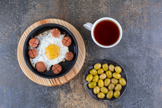 소시지, 올리브, 차 한 잔을 곁들인 계란 프라이
