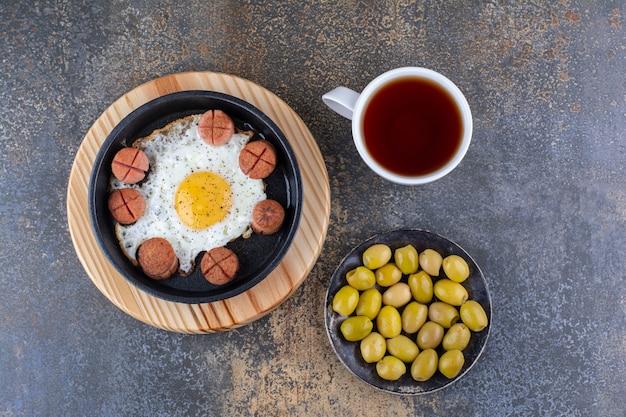 Uovo fritto con salsicce, olive e una tazza di tè