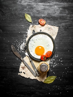 Fried egg with spices on a black wooden background