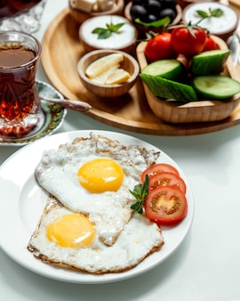 Fried egg with tea and vegetables