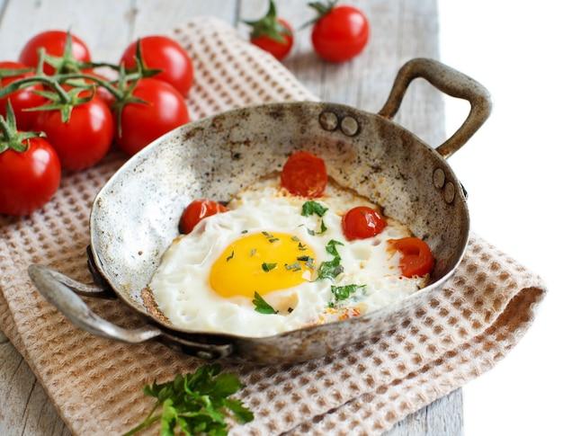 Жареные яйца с помидорами и зеленью на старой сковороде на дереве