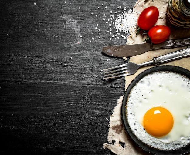 トマトと塩で目玉焼き。黒い木製の背景に。
