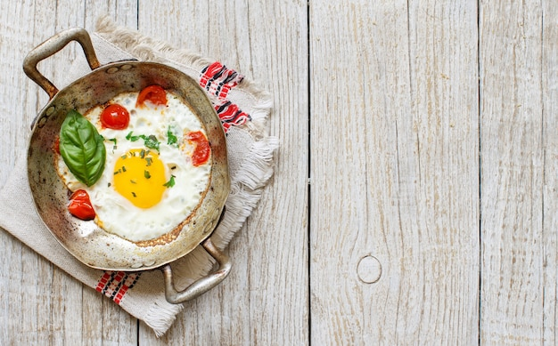 Fried egg with tomatoes and herbs n a old frying pan on wood top view with copy space