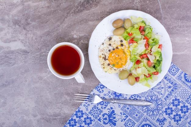 Жареное яйцо с овощным салатом и чашкой чая.