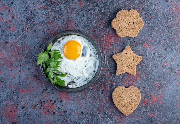 Жареное яйцо с овощами и ломтиками хлеба в форме сердца.
