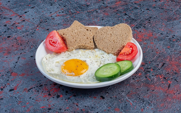 Fried egg with vegetables and heart shape bread slices.