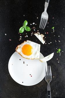 Жареный яичный желток и белая вилка для еды омлет свежее блюдо и ингредиенты