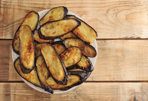 Fried eggplant on the plate on rustic wooden surface