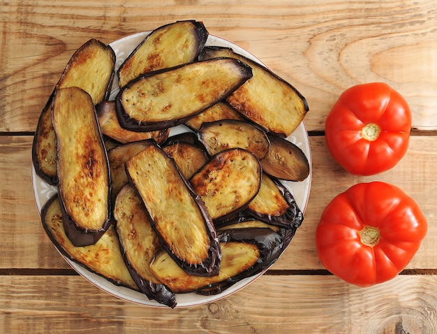 Fried eggplant on the plate and two tomatoes