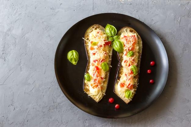 Жареные баклажаны, фаршированные помидорами, тертым сыром, йогуртовой заправкой и клюквой на сером шифере