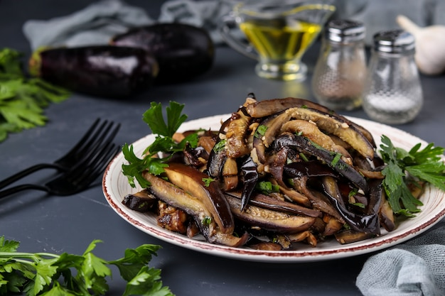 Fried eggplants with garlic and soy sauce, sliced in stripes, in a plate against a dark