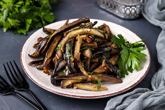 Fried eggplants with garlic and soy sauce, sliced in stripes