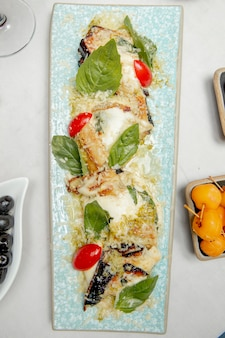 Fried eggplants with grated cheese tomatoes and greens