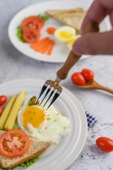 Uova fritte, pane, carote e pomodori su un piatto bianco per la colazione, messa a fuoco selettiva palmare con una forchetta.