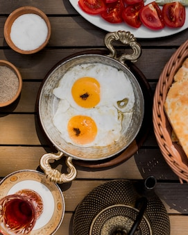 Fried eggs in copper ethnic pan with tea glass and tomatoes around.