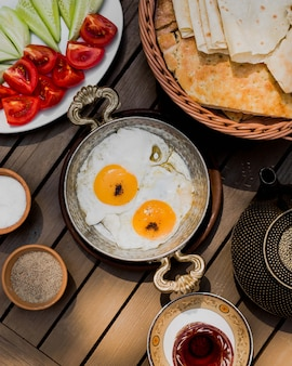 Fried eggs in a copper pan with vegetables and bread.
