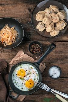 Жареные яйца, пельмени и капуста на деревянном фоне. вид сверху. понятие о кулинарных традициях.