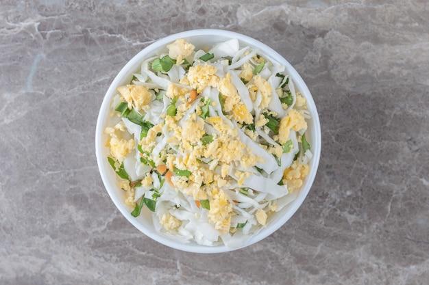 Uova fritte e insalata fresca in una ciotola bianca.