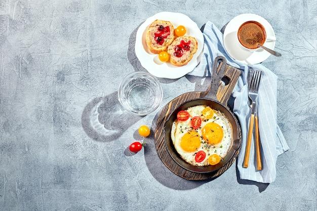 젖통. 주철 냄비에 체리 토마토와 마이크로 그린, 토스트 및 커피 한잔과 함께 두 개의 계란에서 튀긴 계란. 화창한 아침 아침 식사 개념입니다. 평면도.