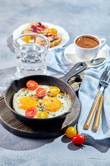 젖통. 주철 냄비에 체리 토마토와 마이크로 그린, 토스트 및 커피 한잔과 함께 두 개의 계란에서 튀긴 계란. 화창한 아침 아침 식사 개념