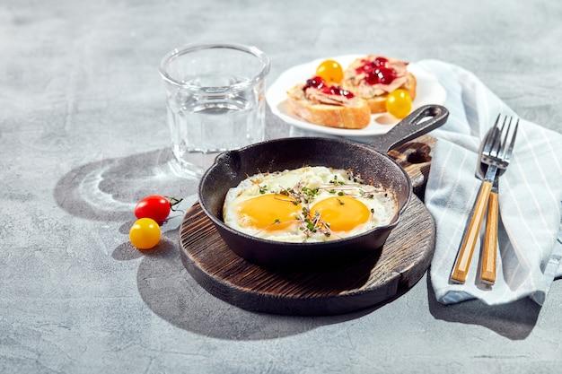 젖통. 주철 냄비에 체리 토마토와 마이크로 그린, 토스트와 함께 두 개의 계란에서 튀긴 계란. 화창한 아침 아침 식사 개념