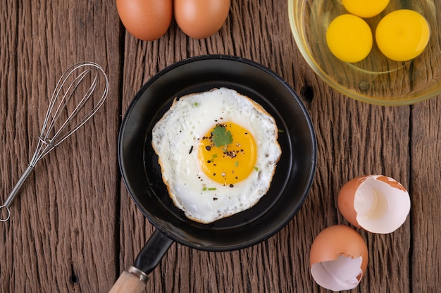 Fried eggs in a frying pan and raw eggs, organic food for good health, high in protein