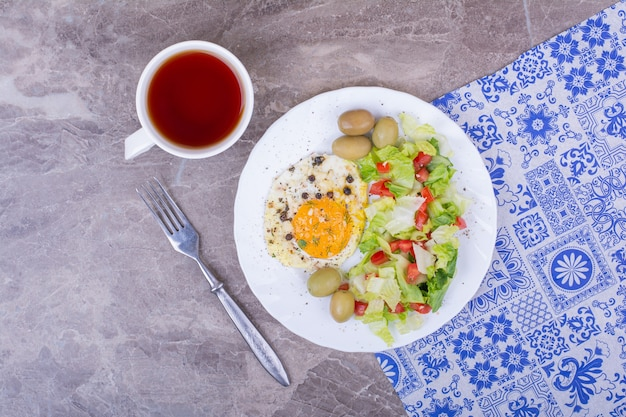 Fried eggs and green salad with a cup of tea