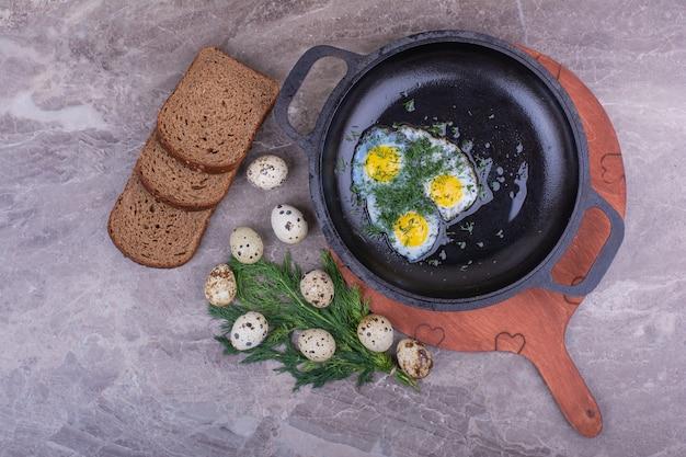 Жареные яйца в металлической сковороде с ломтиками хлеба.