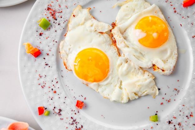 Яичница в тарелку на белом фоне. вид сверху.