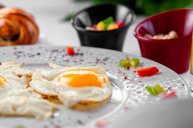 Яичница в тарелке сверху на тесто на фоне