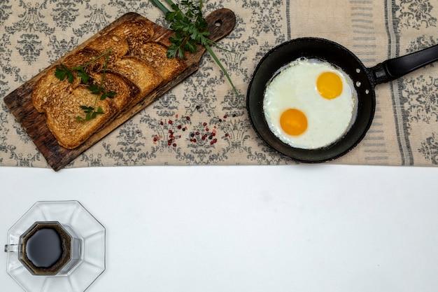Жареные яйца в деревенской железной сковороде, тосты на деревянной доске и чашка кофе на завтрак. вид сверху