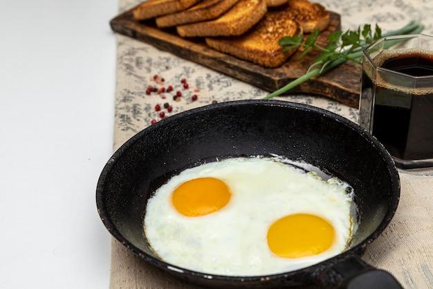 Жареные яйца в деревенской железной сковороде, тосты на деревянной доске и чашка кофе на завтрак.
