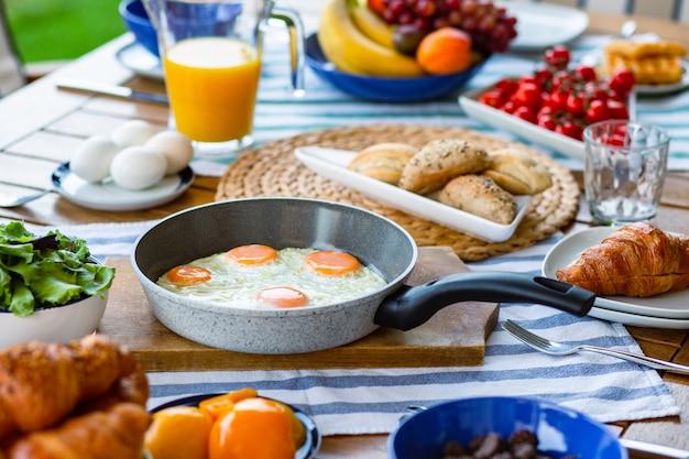 Яичница в сковороде на большом столе, заполненном продуктами яичница на сковороде на завтрак