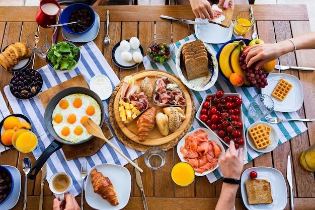 食べ物でいっぱいの大きなテーブルの上のフライパンで目玉焼き目玉焼き朝食テーブル夏