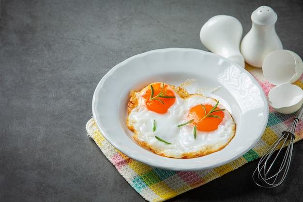 Жареные яйца в белой тарелке на темной поверхности