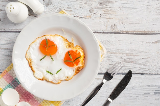 흰색 나무 표면에 흰색 접시에 튀긴 계란